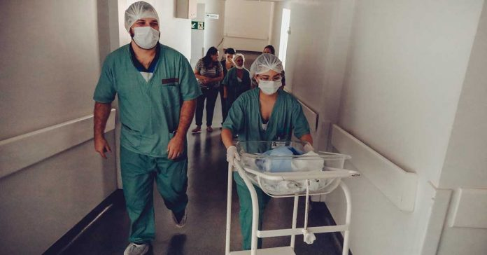 unrecognizable obstetrician and nurse carrying newborn baby trolley in hospital